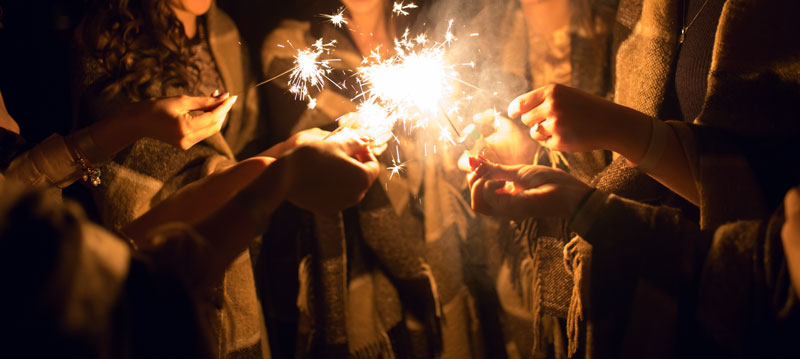 group of people in a huddle with sparklers